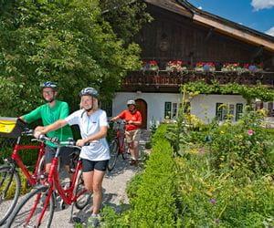 Eurobike-cyclists in front of a beautiful farmhouse in Garmisch Partenkirchen