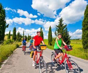 Radfahrer in einer Zypressenallee in der Chianti Gegend