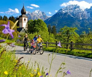 Family is riding bike, in the background the mountains and a church