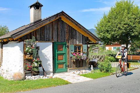 Radler neben kleiner Holzhütte