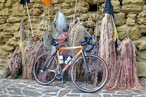 Bike leaning on a wall with fishing nets