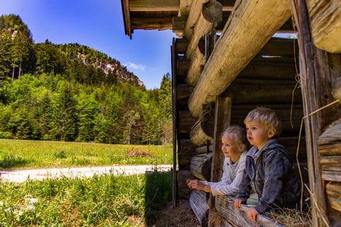 Kinder blicken aus der Holzhütte am Radwegrand