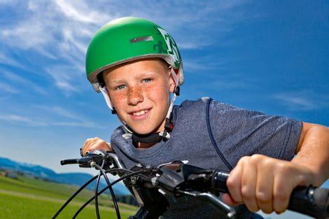 Kind mit grünem Helm auf Fahrrad im Salzburger Seenland