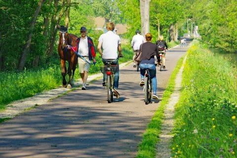 Radfahrer fahren entlang eines Kanals durch das Elsass
