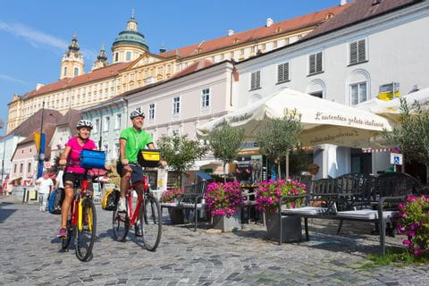 Cyclists in Melk with Abbey in the background
