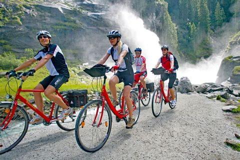 Gruppe von Radfahrern vor einem Wasserfall