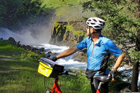 Cyclist in front of waterfalls in Krimml