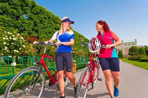 Radfahrer schieben deren Rad durch den Wiener Volksgarten