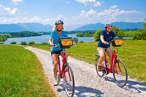 Zwei Radfahrer mit dem Riegsee im Hintergrund