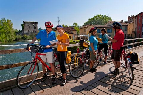 Cyclists having a conversation on a bridge