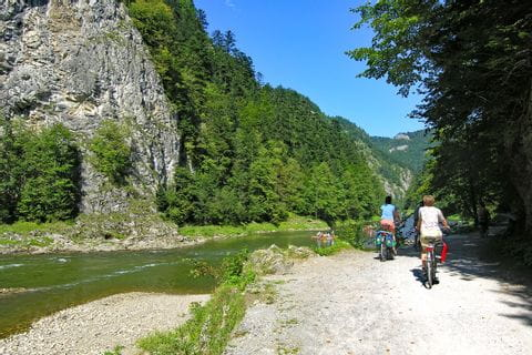 Cyclists beside river at Dunajec bike path