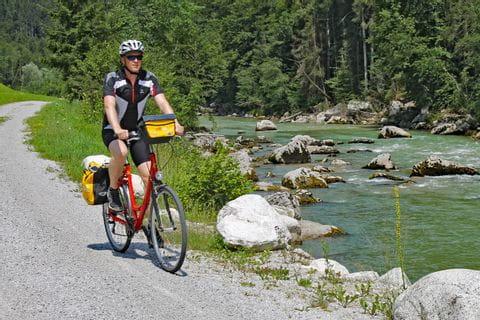 Radfahrer auf Radweg entlang eines Flusses