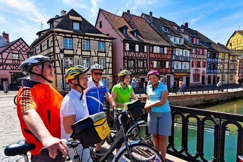 Radfahrer machen Pause am Kanal in Colmar mit butnen Fachwerkhäuser im Hintergrund