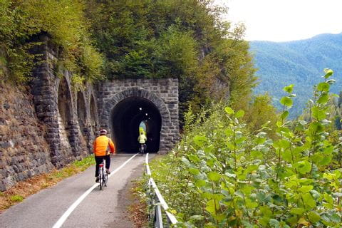 Cyclists biking into a tunnel