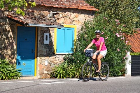 Radfahrerin vor Haus mit bunter Tür und Fenster