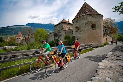 Cyclists passing a small castle in Glurns