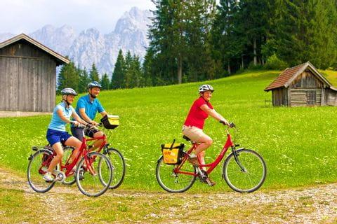 Drei Radfahrer mit Wiese und Heuhütten im Hintergrund