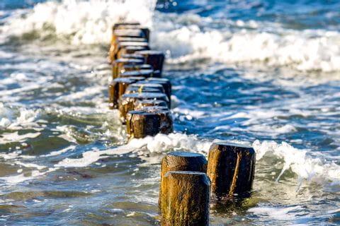 Holzpfeiler die von Wellen umspühlt werden