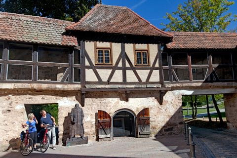 Cyclists in front of frame house in Ansbach