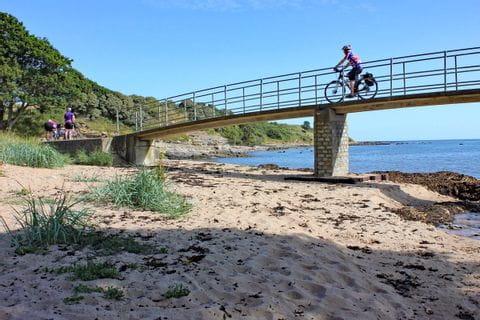 Radweg führt über eine Brücke über dem Strand