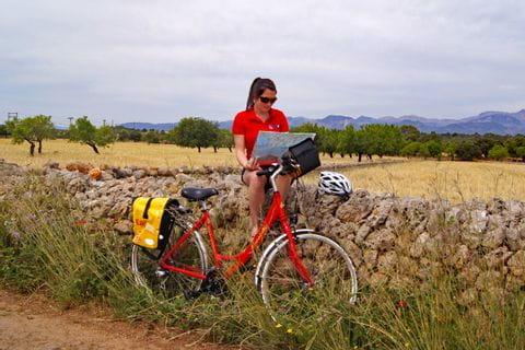 Radfahrerin auf Steinmauer sitzend