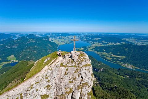Summit cross at the mountain Schafberg with view to Lake Mondsee