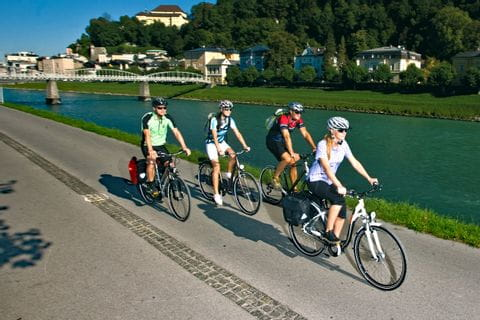 Cyclists biking along the river Salzach