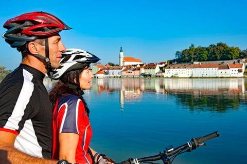 Radfahrer blicken über den Fluss nach Schärding