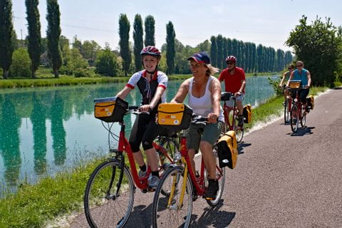 Cyclists biking along the river Adige