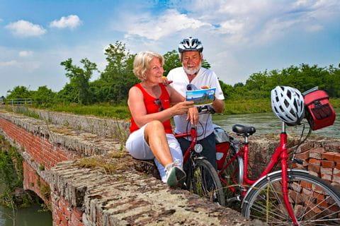 Cyclists having a break on a small bridge in Santhià