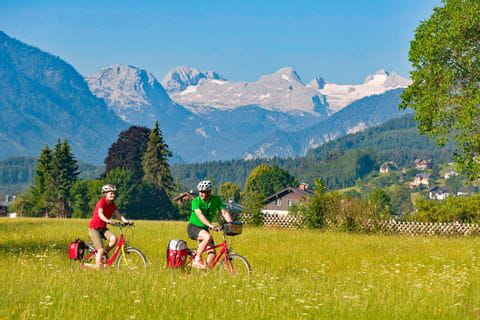 Cyclists in front of mountain Dachstein