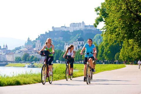 Radfahrer in Salzburg mit Festung Hohensalzburg