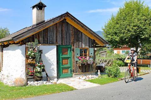 Radfahrer vor kleiner Holzhütte