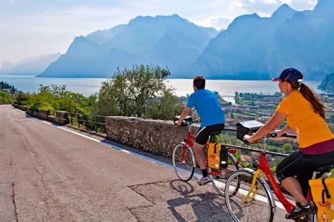 Cyclists biking towards Lake Garda