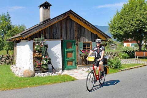 Radler vor kleiner Holzhütte