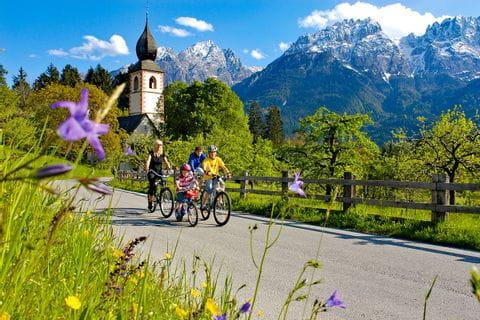 Familie fährt Rad, im Hintergrund die Berge und eine Kirche