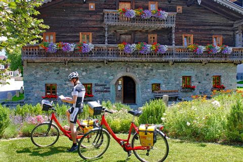 Cyclist in front of old farm house