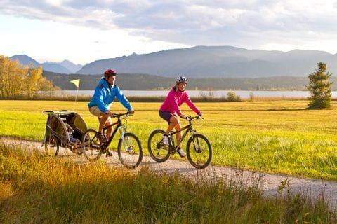 Radfahrer mit Kinderanhänger radeln durch die schöne Landschaft