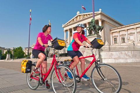 Im Hintergrund der Radfahrer das Wiener Parlament