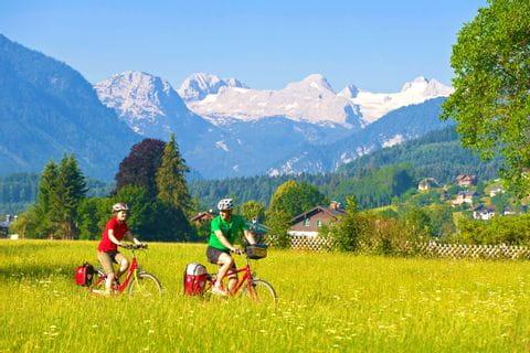 Radfahrer inmitten grüner Landschaft mit Bergpanorama