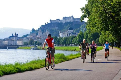 Cyclists at the bank of the river Salzach in Salzburg