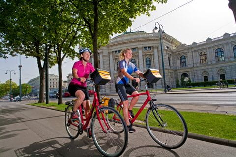 Radfahrer mit dem Wiener Burgtheater im Hintergrund