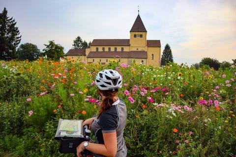 Radfahrer blickt auf eine Kirche mit einer bunten Blumenwiese im Vordergrund