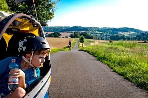Familie radelt entlang dem Weser-Radweg mit einem Kinderanhänger