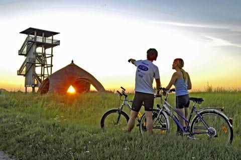 Radler blicken auf Schilfhütte bei Sonnenuntergan