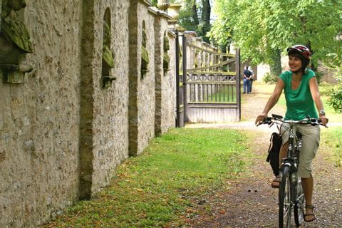 Cyclist enfront of stone wall