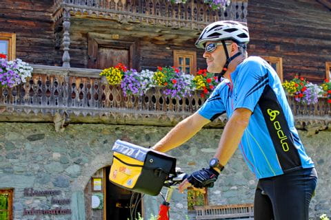 Radfahrer vor Holzhaus mit Blumen