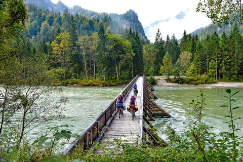 Radfahrer fahren über eine Brücke an der Enns