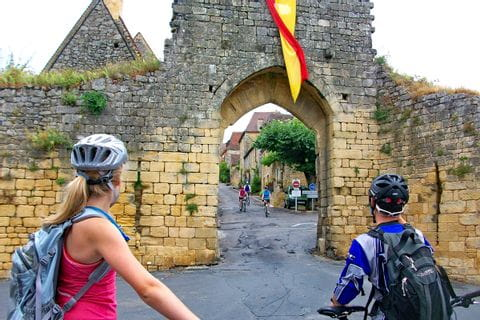 Cyclists in front of the Porte del Bos in Domme