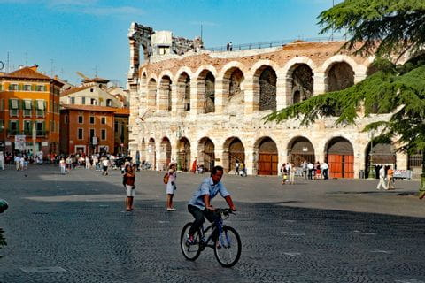 A cyclist in fron of the Arena in Verona